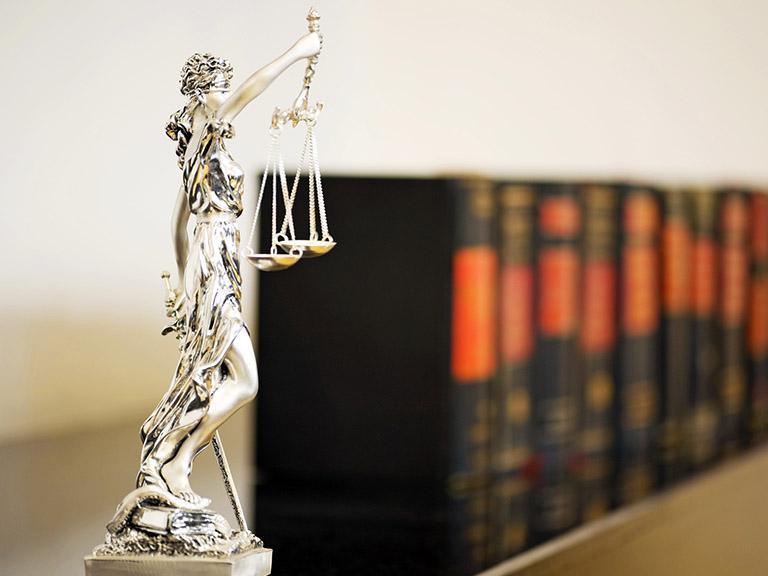 Temida bogini sprawiedliwości natle ksiąg